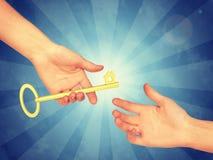 Hand som passerar en guld- tangent arkivbild