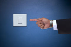 Hand som pekar till strömbrytaren av den elektriska anordningen fotografering för bildbyråer