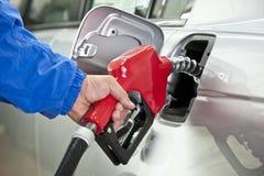 Hand som pumpar bensin från röd dysa för bränslepump royaltyfri fotografi