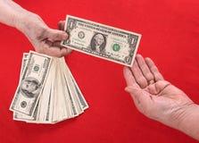 Hand som räcker över pengar till en annan hand Royaltyfri Foto