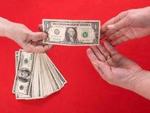 Hand som räcker över pengar till en annan hand Royaltyfri Bild