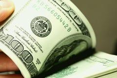 Hand som räknar pengardollarcloseupen Arkivfoto