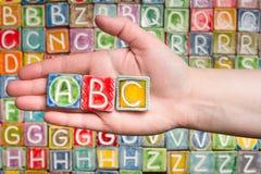 Hand som rymmer abc-bokstäver Arkivfoto