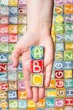 Hand som rymmer abc-bokstäver Arkivfoton