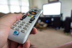 Hand som rymmer den DirecTv fjärrkontrollen som pekar på TV royaltyfri foto