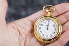 Hand som rymmer den gamla klockan som pekar midnatt Royaltyfri Bild
