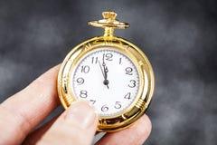 Hand som rymmer den gamla klockan som pekar midnatt Royaltyfri Foto