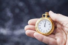 Hand som rymmer den gamla klockan som pekar midnatt Arkivbild