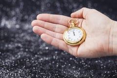 Hand som rymmer den gamla klockan som pekar midnatt Arkivfoton