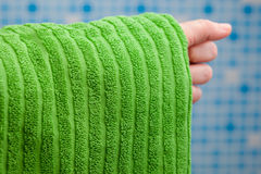 Hand som rymmer den gröna handduken arkivbilder