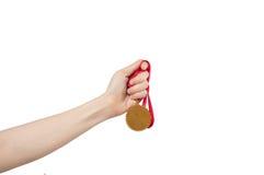 Hand som rymmer den guld- medaljen arkivfoto