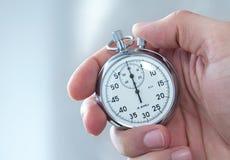 hand som rymmer den mänskliga stopwatchen royaltyfri bild