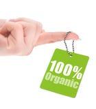 Hand som rymmer 100% den organiska etiketten Fotografering för Bildbyråer