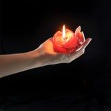 Hand som rymmer den röda stearinljuset Arkivbild