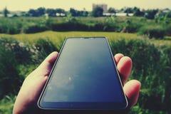 Hand som rymmer den svarta smartphonen med den svarta skärmen mot suddig trädgårdbakgrund fotografering för bildbyråer