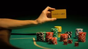 Hand som rymmer det guld- kortet som spelar chiper på tabellen, olaglig kasino för Storgubbe-klienter lager videofilmer