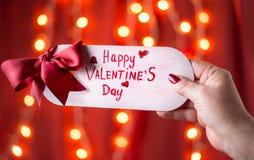 Hand som rymmer det lyckliga valentindagkortet royaltyfri bild
