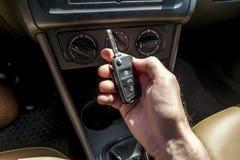 Hand som rymmer en biltangent i bilen Arkivfoto