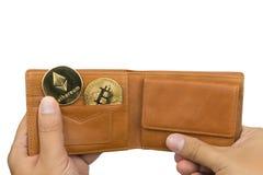 Hand som rymmer en brun läderplånbok med en bitcoin och ett ethereummynt royaltyfri bild