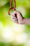 Hand som rymmer en carabine på ett rep Klättringutrustning som isoleras på en vit bakgrund Arkivfoton