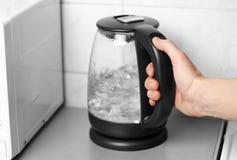 Hand som rymmer en exponeringsglastekanna med det svarta handtaget close upp arkivfoto