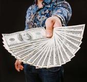 Hand som rymmer en fan av dollar Hundra dollar sedlar buntar, styckar i lotter dollar, lott av sedlar Arkivfoton