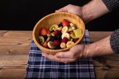 Hand som rymmer en fruktsalladbunke klar att äta mycket sunt och peka för finger royaltyfria bilder
