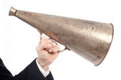 Hand som rymmer en gammal megafon Arkivfoto