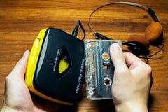 Hand som rymmer en gammalmodigt b?rbart kassettspelare och kassettband arkivbild