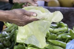 Hand som rymmer en gul plastpåse på livsmedelsbutiken fotografering för bildbyråer
