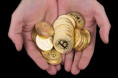 Hand som rymmer en hög av guld- bitcoins Royaltyfria Foton