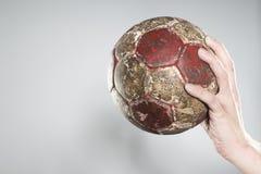 Hand som rymmer en handboll Arkivbild