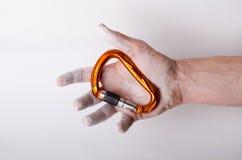 Hand som rymmer en karbin på ett rep Klättringutrustning på en vit bakgrund Fotografering för Bildbyråer