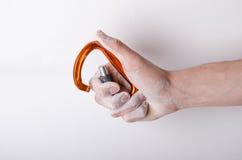 Hand som rymmer en karbin på ett rep Klättringutrustning på en vit bakgrund Royaltyfria Bilder