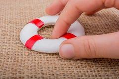 Hand som rymmer en Lifesaver på tyg Arkivbild