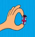 Hand som rymmer en liten mycket liten gåva Arkivbild