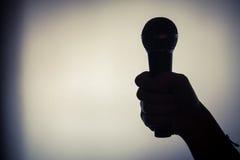 Hand som rymmer en mikrofon Arkivfoto