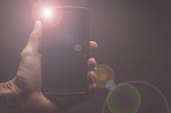 Hand som rymmer en mobiltelefon med exponeringen royaltyfria foton