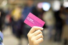 Hand som rymmer en pappers- biljett på suddig backgroun royaltyfria bilder