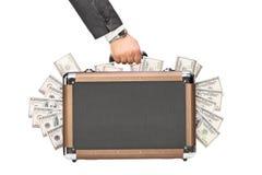 Hand som rymmer en portfölj full av pengar Royaltyfri Fotografi