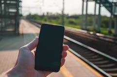 Hand som rymmer en smartphone med järnvägsstationen i bakgrunden arkivfoton