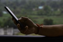Hand som rymmer en telefon med suddig bakgrund royaltyfria bilder