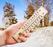 Hand som rymmer en termometer Arkivbild