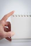Hand som rymmer en tom anteckningsbok Arkivbild
