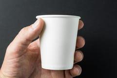 Hand som rymmer en vitbokkopp för varmt te och kaffe på svart bakgrund, modell royaltyfria foton