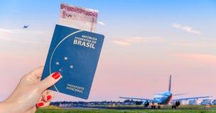 Hand som rymmer ett brasilianskt pass med en 5 reais anmärkning inom Arkivbilder