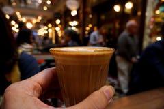 hand som rymmer ett exponeringsglas av kaffe arkivbild