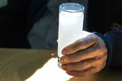 Hand som rymmer ett exponeringsglas med ouzo royaltyfri fotografi