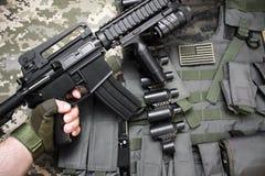 Hand som rymmer ett gevär på militär kamouflagebakgrund Fotografering för Bildbyråer