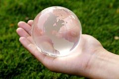 Hand som rymmer ett glass jordklot arkivbilder